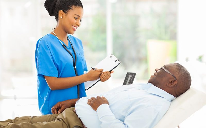 beautiful african female doctor consulting senior patient in office